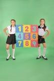 2 девушки школы держат доску цвета с номером Стоковое фото RF