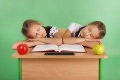 2 девушки школы спать на стоге книг на ее столе Стоковые Изображения