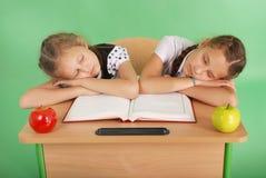 2 девушки школы спать на стоге книг на ее столе Стоковая Фотография