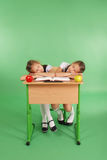 2 девушки школы спать на стоге книг на ее столе Стоковое Фото
