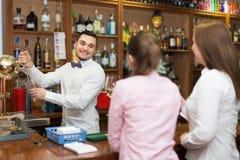 2 девушки flirting с барменом Стоковые Изображения