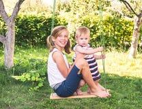 девушки outdoors 2 милых маленьких сестры имея потеху на качании к Стоковые Фото
