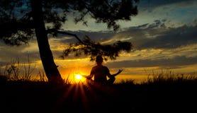 девушки silhouette в раздумье в положении лотоса на заходе солнца Стоковые Изображения RF
