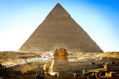 Египетский сфинкс с ptramid в предпосылке Стоковые Изображения