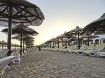Египет: Дезертированный пляж оборудованный с шезлонгами и зонтиками - в вечере, на заходе солнца стоковые изображения rf