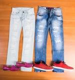 Его и ее голубые джинсы положенные с ботинками Стоковые Фото