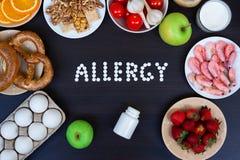 Еда аллергии как молоко, апельсины, томаты, чеснок, креветка, арахисы, яйца, яблоки, хлеб, клубники на деревянном столе стоковая фотография rf