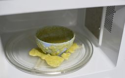Еда взорвала в микроволновой печи - предупреждающей печи с переполнением еды чашки стоковая фотография