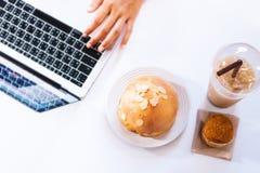 Еда высококалорийной вредной пищи и сладостного хлеба на компьютере стоковое фото