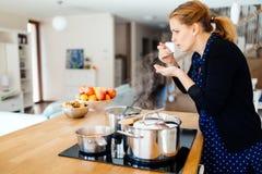 Еда дегустации домохозяйки будучи деланным в кухне Стоковое Изображение RF