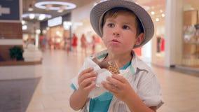 Еда детей, милый счастливый ребенк в шляпу есть донут шоколада в торговом центре акции видеоматериалы