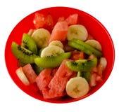 еда диетпитания арбуз, киви, виноградины, банан на плите изолированной на белой предпосылке Фруктовый салат на плите стоковое фото