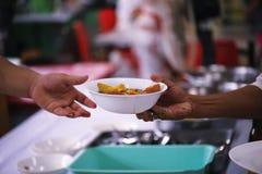 Еда доли волонтеров к бедным для того чтобы сбросить голод: Концепция призрения стоковая фотография