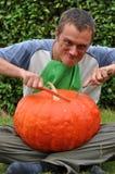 еда его огромных детенышей тыквы человека Стоковая Фотография