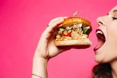 еда женщины сандвича Счастливая девушка ест гамбургер Она раскрыла ее рот, держа гамбургер в ее правой руке стоковое изображение rf