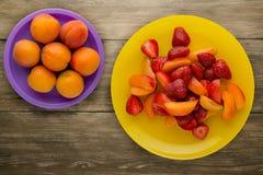 еда здоровая Клубники и абрикосы на плите предпосылка fruits деревянно стоковые фото