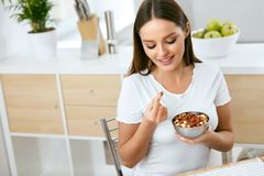 еда здоровая Счастливая женщина есть гайки Стоковое фото RF