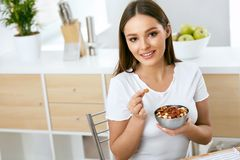 еда здоровая Счастливая женщина есть гайки Стоковая Фотография