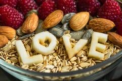 Еда здорового шара завтрака Слово ВЛЮБЛЕННОСТЬ в плите с здоровой едой Поленика, банан, гайки Вегетарианская принципиальная схема стоковое фото