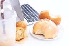 еда и сладостный хлеб на столе компьютера стоковое изображение rf