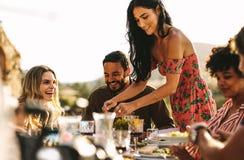Еда красивой женщины служа к друзьям стоковые изображения