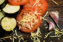 Еда лета: отрезанные баклажан и томат Томаты, aubergines, сыры, чеснок и сельдерей на деревянной доске Стоковые Изображения