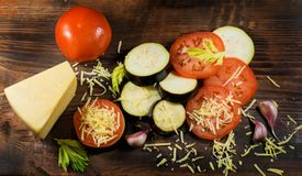 Еда лета: отрезанные баклажан и томат Томаты, aubergines, сыры, чеснок и сельдерей на деревянной доске Стоковые Фотографии RF