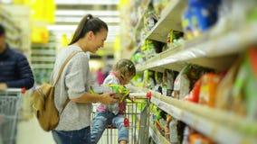 Еда молодой привлекательной мамы и маленького ребенка покупая в супермаркете Красивая женщина при милая девушка стоя близко полка сток-видео