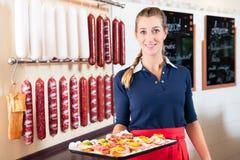 Еда пальца женщины предлагая и маленькие укусы в магазине мяса стоковые изображения