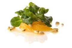 Еда перста с померанцем, салатом поля и гайками сосенки Стоковая Фотография RF