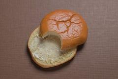 Еда плюшки гамбургера в верхнем угловом взгляде на предпосылке ткани стоковая фотография
