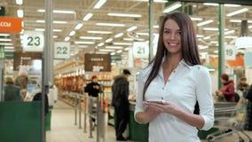 Еда покупок женщины в предпосылке супермаркета Закройте вверх по продуктам покупки девушки взгляда используя цифровое устройство  видеоматериал