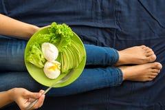 еда принципиальной схемы здоровая ` S женщин вручает держать плиту с салатом, кусками авокадоа и краденными яичками Стоковое Фото