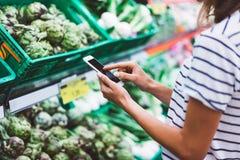 Еда приобретения покупок молодой женщины здоровая в предпосылке нерезкости супермаркета Закройте вверх по продуктам покупки девуш Стоковые Фотографии RF