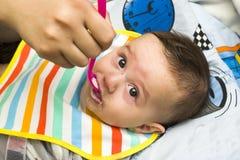 Еда руки ` s женщины подавая к маленькому ребёнку Стоковые Изображения