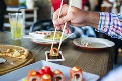 Еда суш крена в японском ресторане, рука с палочками Стоковые Фото