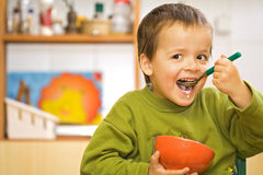 еда хлопьев мальчика счастливая стоковая фотография