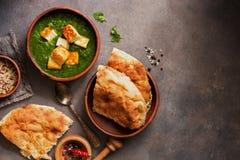Еда Palak Paneer индийская, naan хлеб, рис и специи на темной предпосылке Взгляд сверху, плоское положение, космос экземпляра стоковые изображения rf