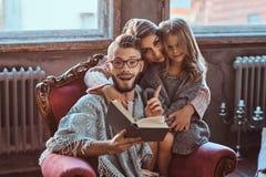 Единение семьи Рассказ чтения мамы, папы и дочери записывает совместно сидеть на кресле Семья и родительство стоковое фото