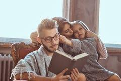 Единение семьи Рассказ чтения мамы, папы и дочери записывает совместно сидеть на кресле Семья и родительство стоковые фотографии rf