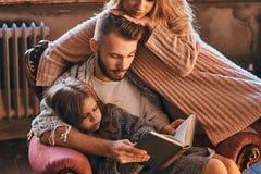 Единение семьи Рассказ чтения мамы, папы и дочери записывает совместно сидеть на кресле Семья и родительство стоковое изображение rf