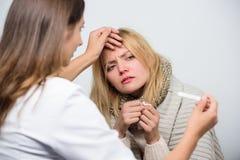Ее лихорадка делает ее дискомфортный Доктор навещая нездоровая женщина дома t r стоковое изображение rf