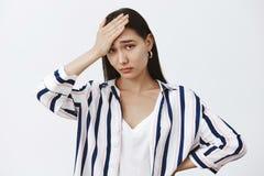 Ее сестра как боль в ишаке Уставшая и хмурая милая женщина в striped блузке, держащ ладонь на лбе, чувствуя вниз стоковая фотография rf
