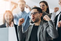 Ежедневные победители Группа в составе счастливые бизнесмены в умной случайной носке смотря ноутбук и показывать жестами Завоеват стоковые фото
