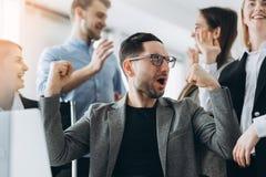Ежедневные победители Группа в составе счастливые бизнесмены в умной случайной носке смотря ноутбук и показывать жестами Завоеват стоковое изображение