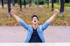 Ежедневный победитель Возбужденный молодой человек держа оружия поднятый и expre стоковое фото