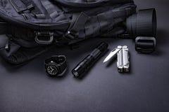 Ежедневный снесите детали EDC для людей в черном цвете - рюкзака, тактического пояса, электрофонаря, дозора и серебряного multi и стоковое изображение
