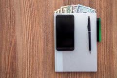 Ежедневный журнал с долларами деноминации на деревянном столе Стоковые Фотографии RF