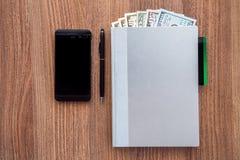 Ежедневный журнал с долларами деноминации на деревянном столе Стоковое фото RF