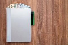 Ежедневный журнал с долларами деноминации на деревянном столе Стоковое Изображение RF